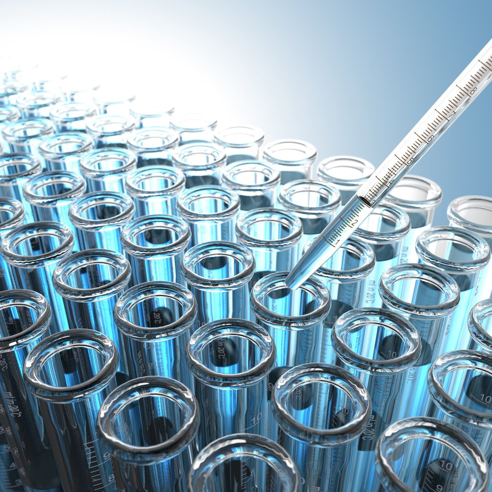 Laboratory Pipette with Blue Liquid Over Glass Test Tubes.